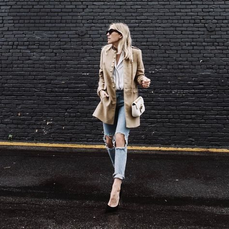 Jacey Duprie pairs a beige, suede, military style overcoat with ripped denim jeans and a white blouse. She matches this outfit with classic black stilettos. Coat: Mango.