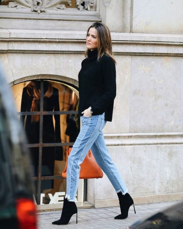 Alex Rivière is wearing a chunky black turtleneck sweater, light wash patchwork jeans and black stiletto ankle boots. Boots: Casa Dei
