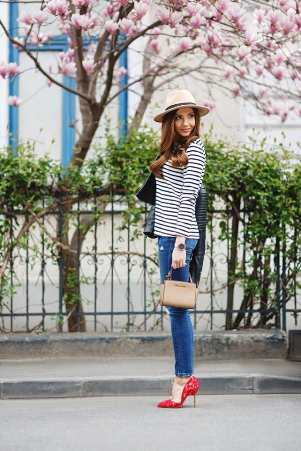 Larisa Costea is wearing a beige fedora, a white and navy striped bateau shirt, medium wash skinny jeans and red lace stiletto heels. Blouse/Hat: Shein, Jacket/Jeans: Zara, Bag: Michael Kors, Shoes: Kurt Geiger, Watch: Kapten & Son