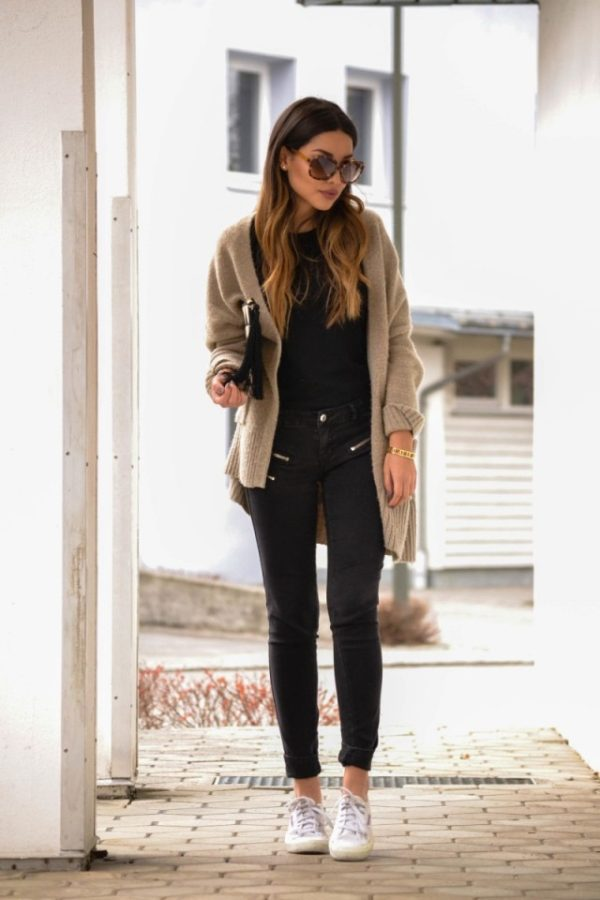 Consuelo Paloma is wearing a beige oversized soft knit cardigan, a black shirt, black jeans with zip detail and white lace up trainers. Cardigan: Zara, Shirt: Asos, Trousers: Mango, Trainers: Super G