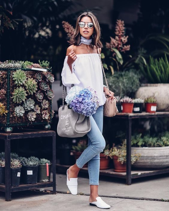Annabelle Fleur is wearing a white tencel off the shoulder top and light wash cropped skinny jeans, with white leather loafers and a grey Chanel tote and blush pink leather Chanel shoulder bag. Top/Jeans: Bella Dahl, Bags: Chanel