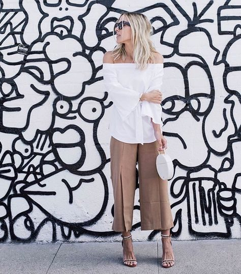 Jacey Duprie wears a flirty off the shoulder bell-sleeved blouse, paired with beige pleated trousers and silver detailed stilettos. Blouse: White House Black Market.