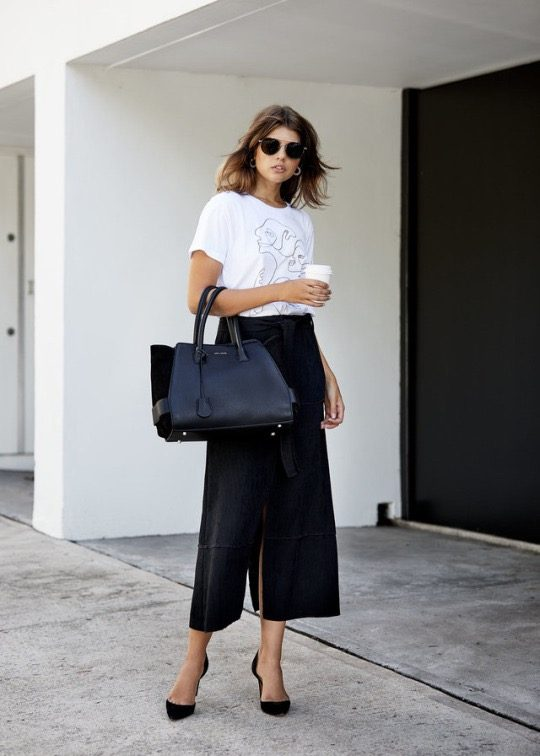 Talisa Sutton is wearing an artist designed white cotton t-shirt, black midi skirt, black suede pumps and a black leather tote bag. T-shirt: Christiane Spangsberg x J.V.Reid, Skirt: Wynn Hamlyn, Bag: Anna White, Sunglasses: Celine, Earrings: Reliquia, Heels: IRO.