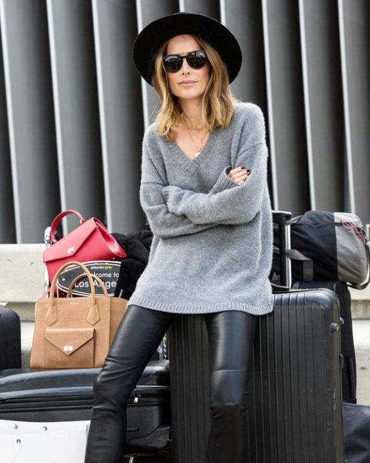 Anine Bing is seen in an oversized marl grey cashmere sweater, worn over leather leggings and paired with shades and a wide set fedora hat. Brands not specified.