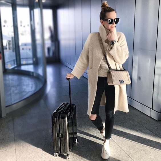 Helena Glazer is wearing a gorgeous cream overcoat paired with a pair of distressed black denim jeans and white sneakers for a comfortable yet stylish travel look! Jeans: Aritzia, Shoes: Sezane, Top: Aritzia.