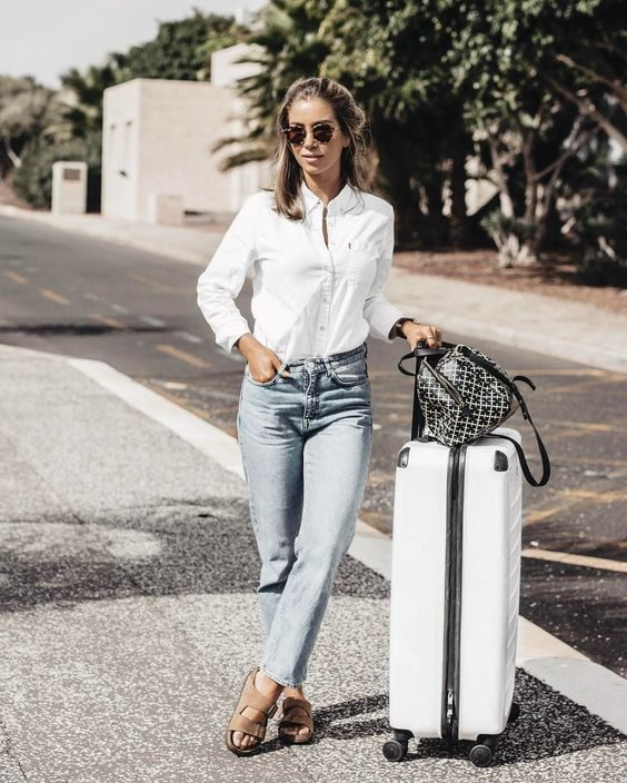 Emilie Tommerberg keeps it simple in a white button up shirt, acid wash jeans, and a pair of beige Birkenstock sandals; the perfect travel combination. Shirt: Lexington Company, Shoes: Birkenstock.