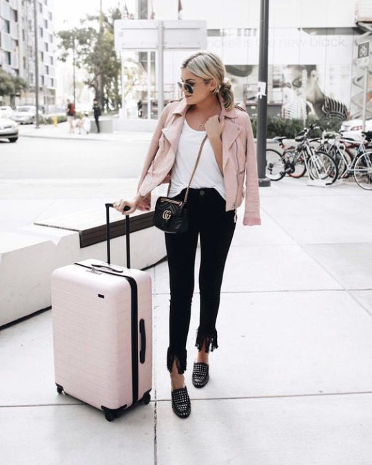 Emily Luciano travels in a stylish combination of pink and black, wearing skinny jeans frayed at the ankle, studded loafers, a white tee, and a gorgeous pink leather jacket. Brands not specified.