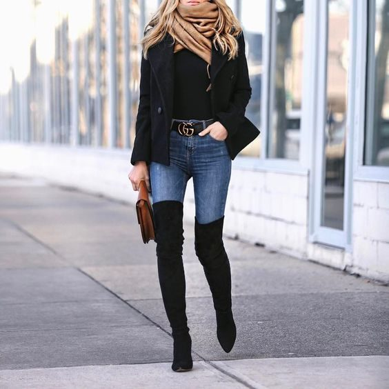 Helena Glazer is seen here in a pair of striking thigh high boots, worn over skinny denim jeans with a statement belt to create a sexy, chic, winter style. She combines these pieces with an oversized beige scarf and black cropped overcoat. Brands not specified.