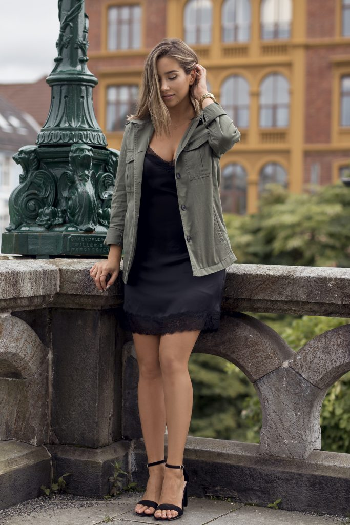 Emilie Tømmerberg is wearing a silk slip dress with lace trim detailing with a short military-style jacket, barely there black sandals, and a chunky oversized gold watch.   Product information not available.