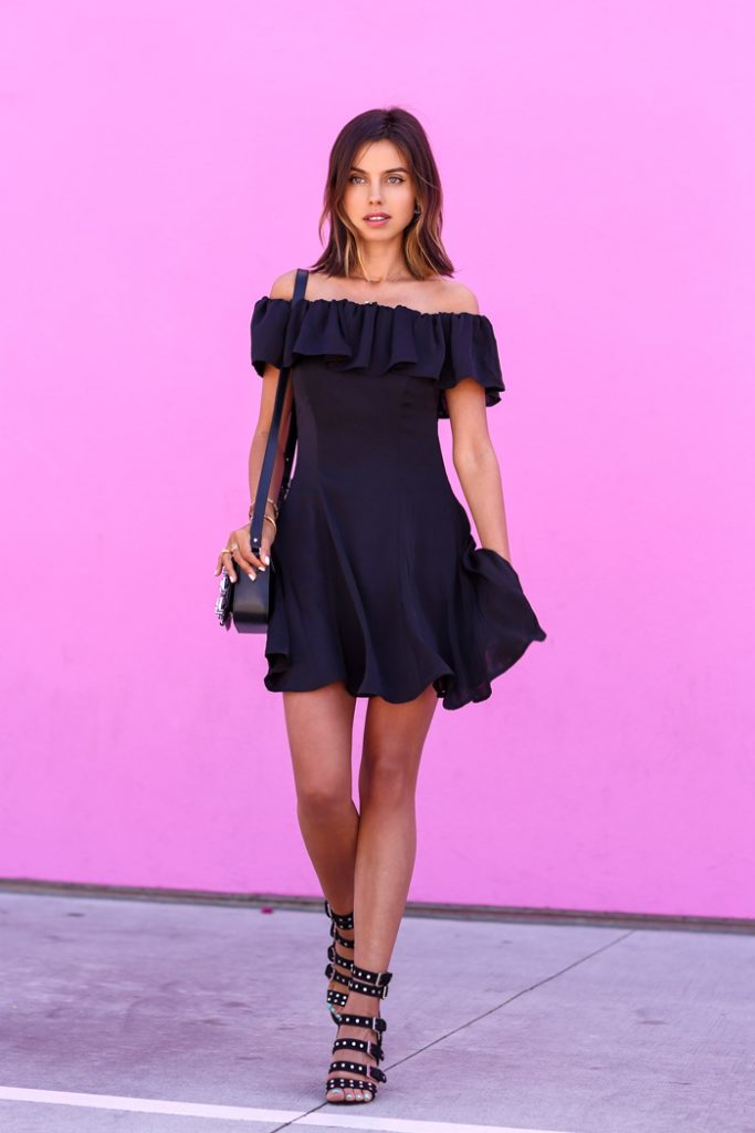 Annabelle Fleur is wearing a Spanish-inspired shoulderless short dress with studded chunky block heels and a matching studded shoulder bag.   Dress: Capulet, Bag: The Kooples, Sandals; Laurence Dacade, Jewelry: Nialaya