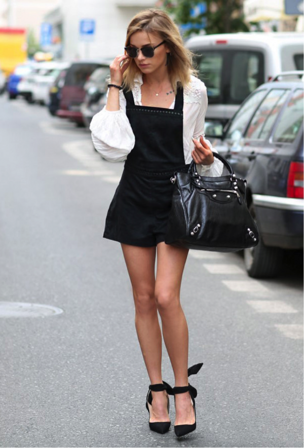 Julietta Kuczyńska is wearing a black overall style dress over a white blouse with oversized lace and chiffon sleeves. The combination is worn with pointed toed bow heels, oversized sunglasses, and a large tote bag. Dress: H&M, Blouse: Zara, Bag: Balenciaga, Shoes: Zara, Glasses: Parfois