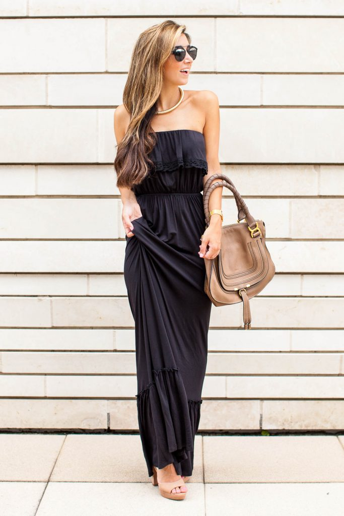 Jessi Afshin is wearing a strapless maxi dress with a frill detail on the bust, a thick gold rope necklace, nude platform sandals, and a matching nude oversized handbag.   Maxi Dress: Felicity and Coco, Necklace: Sole Society, Platform Sandals: Vince Camuto, Bag: Chloe.
