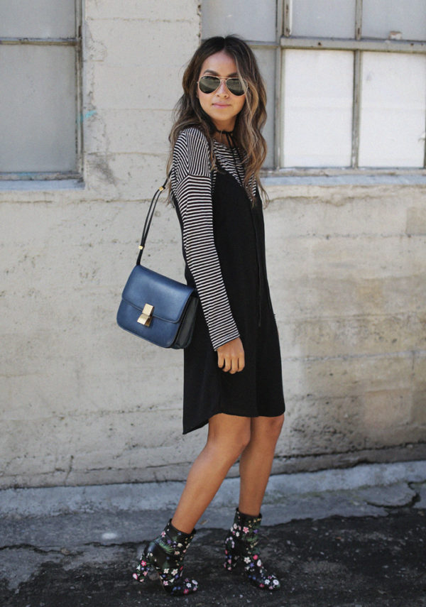 Julie Sarinana is wearing a black cotton slip dress over a simple black and white striped long sleeved tee, with a small square navy shoulder bag and floral ankle boots. Dress: Simply Jules, Boots: Valentino, Striped Tee: Paige, Bag: Celine.