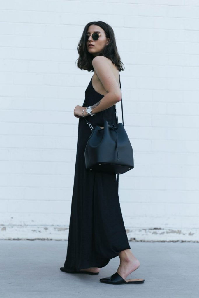 Sophie Van Daniels is wearing a maxi length black cotton gown with an oversized draw string shoulder bag, round slim line sunglasses, and flat black slip on mules.   Dress: Zara, Mules: H&M, Bag: Agneel, Sunglasses: Ray Ban