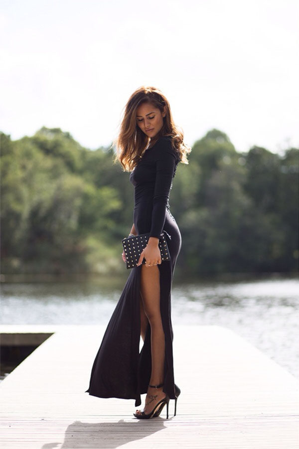 Sharareh Sophia Hosseini is wearing a high necked and tightly fitted maxi dress slit to the thigh, paired with high black stiletto heels and a studded clutch bag.   Product information not available