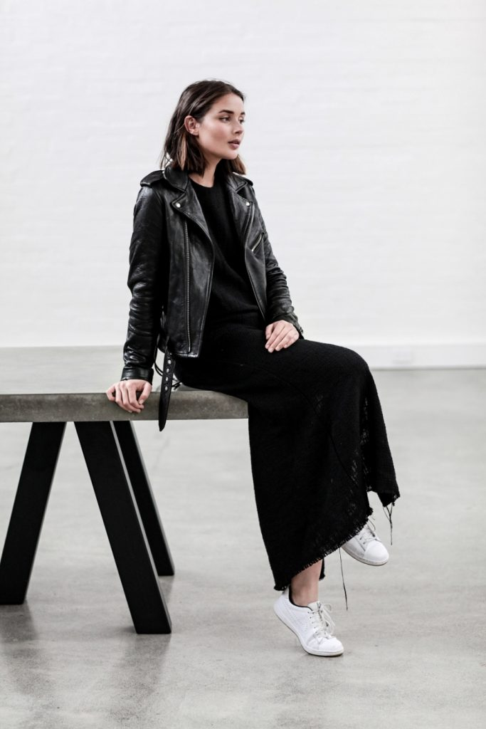 Sara Donaldson is wearing a black maxi dress with a t shirt collar and a raw hem, a black leather biker jacket, and simple white sneakers   Dress: Matin, Leather Jacket: IRO, Shoes: Nike