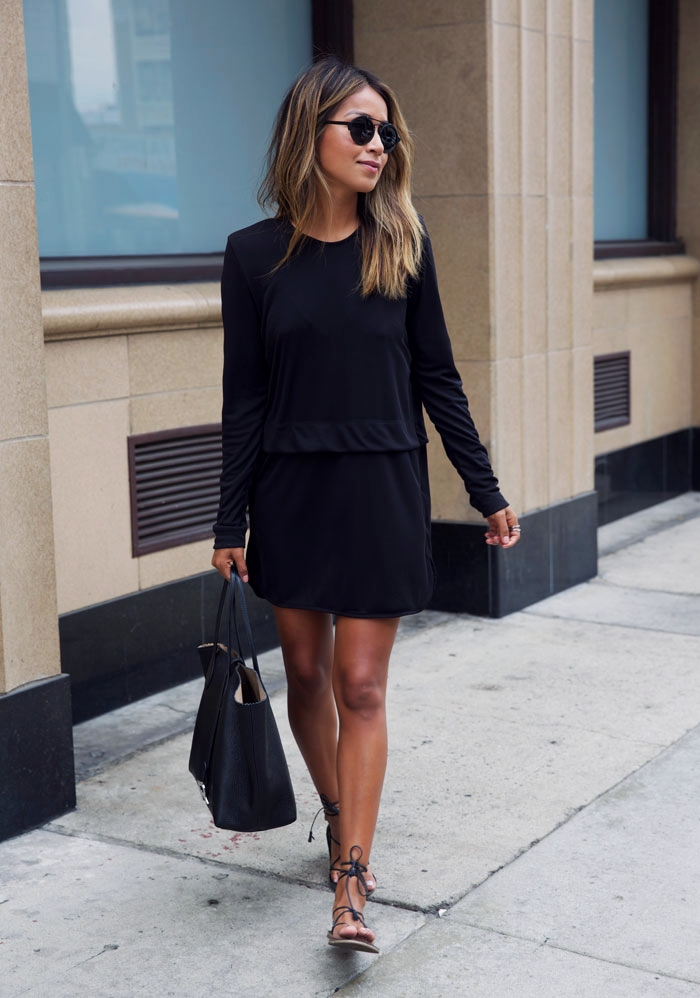 Julie Sarinana is wearing a black T-shirt dress with a dropped waist paired with laced black sandals, a black tote, and oversized black sunglasses.    Dress: Sincerely Jules, Sunglasses: Illesteva, Tote Bag: ROCHAS