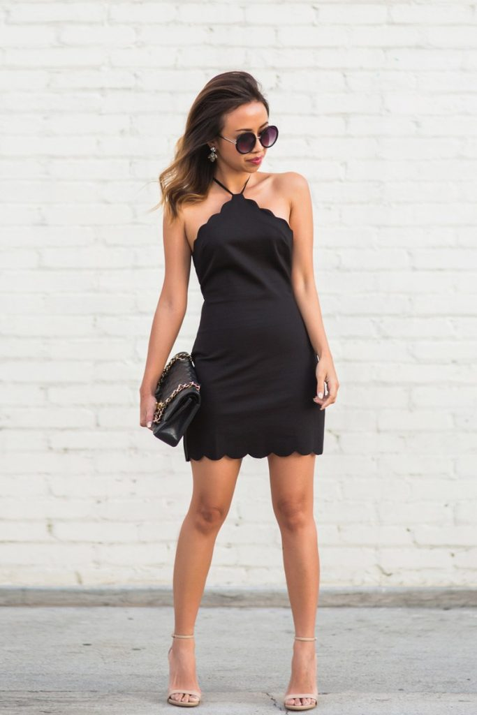 Kim Le is wearing a short black scallop dress with a halterneck, nude spaghetti stap heel sandals, a boxy bag with a metal chain stress and square sunglasses.  Dress: Urban Outfitters, Shoes: Steve Madden, Handbag; Chanel, Sunglasses: Nordstrom.