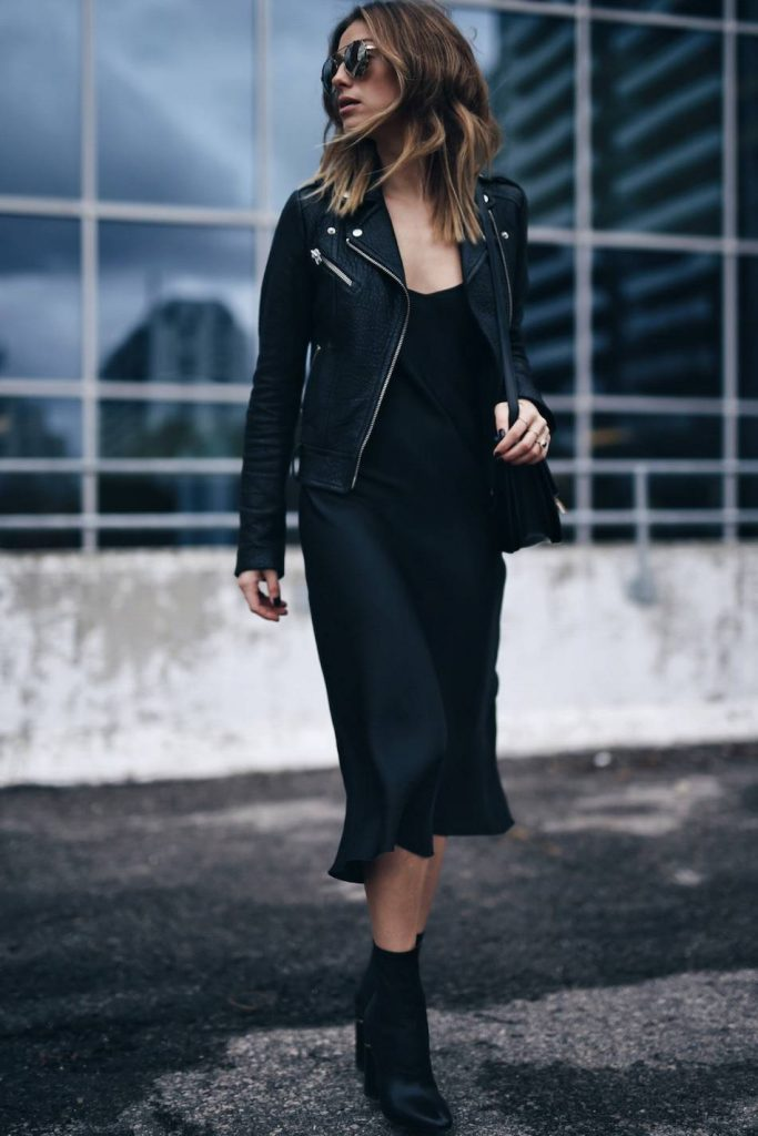 Jill Lansky is wearing a mid-length black slip dress, a minimalist black leather jacket with silver hardwear, and simple black ankle boots.   Dress: Organic by John Patrick, Leather Jacket: Mackage, Bag: Celine, Boots: Philip Lim.