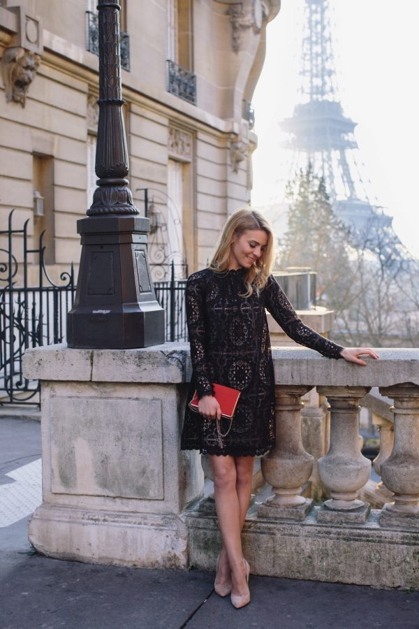 Katarzyna Tusk is wearing a simple black lace shift dress in an above-knee length paired with nude and gold heels and a red box clutch. Dress: Temperley, Shoes: Moliera2, Bag: Zara.