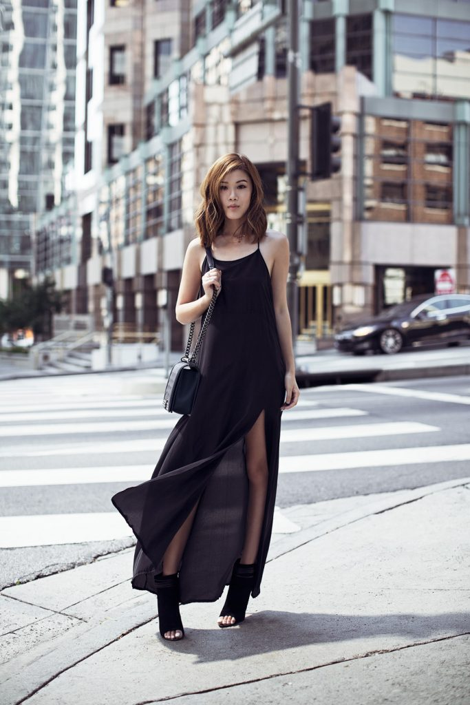Jenny Tsang is wearing a black maxi dress with a deep thigh slash and spaghetti strap detailing, heeled bootie sandals, and a boxy purse with metallic studding on the strap.   Dress: Anine Bing, Bag: Chanel, Shoes: Dolce Vita.