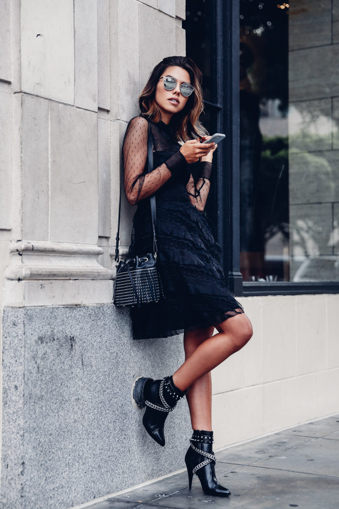 Annabelle Fleur is wearing a black lace button up dress with ruffle detailing, teamed with black and silver embellished heeled ankle boots, a black studded drawstring bag, and oversized shades. Dress: REDValentino, Booties: Yves Saint Laurent, Bag: Yves Saint Laurent.
