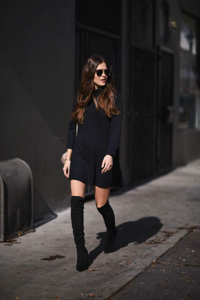 Paola Alberdi is wearing a black ribbed high neck swing shift dress, over-the-knee black suede heeled boots, and a cream leather bag with metal rimmed sunglasses.  Dress: Glamorous, Boots: Joie, Sunglasses: Dior, Handbag: Chloe Faye.