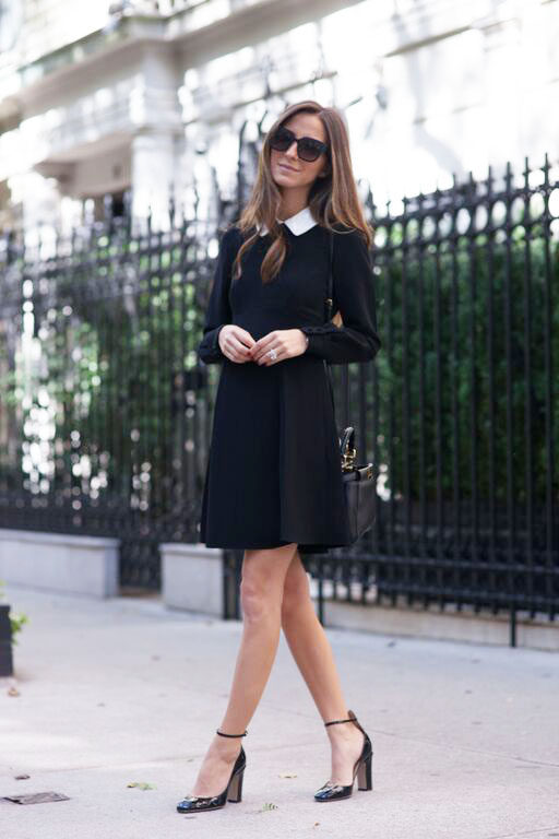 Arielle Nachami is wearing a short black swing dress with a crisp white collar which she has paired with a simple black shoulder bag, heeled patent black shoes with a skinny ankle strap and oversized square shades. Dress: Kate Spade.