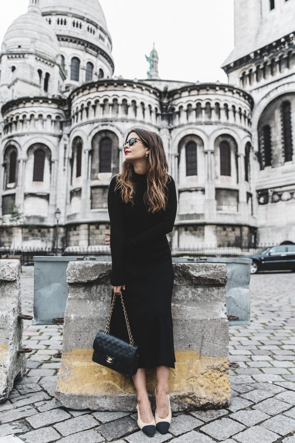Sara Escudero is wearing an on-trend fitted midi length dress with a high neckline, a classic black handbag with a metallic strap, and monochrome pumps. Dress: Zara, Bag: Chanel, Shoes: Chanel.