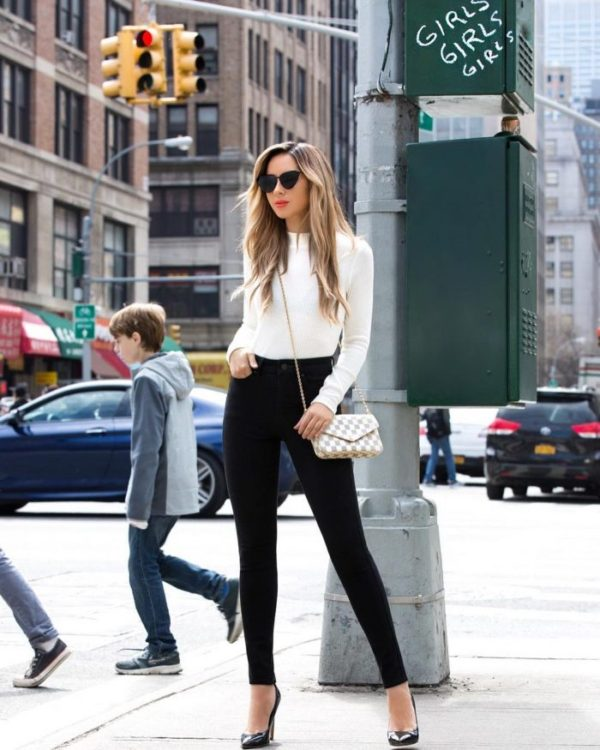 Jasmin Howell keeps it simple, wearing black jeans with a white long sleeved top, patent leather heels, and a petite cross body bag. Jasmin adds a touch of glamour to this look with black shades. Top: Uniqlo.