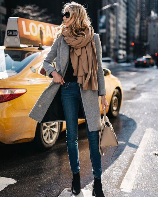 Amy Jackson wears this grey overcoat with a beige blanket-style scarf, paired with a black top, boots, and jeans for an easy, achievable spring style. Brands not specified.