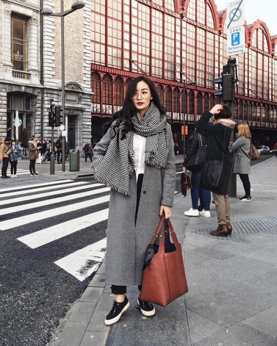 Levi wears a grey maxi coat with black jeans, a white button up blouse, a black and white gingham blanket scarf, and black sneakers. This look is completed with a large leather handbag, and wide framed glasses. Brands not specified.