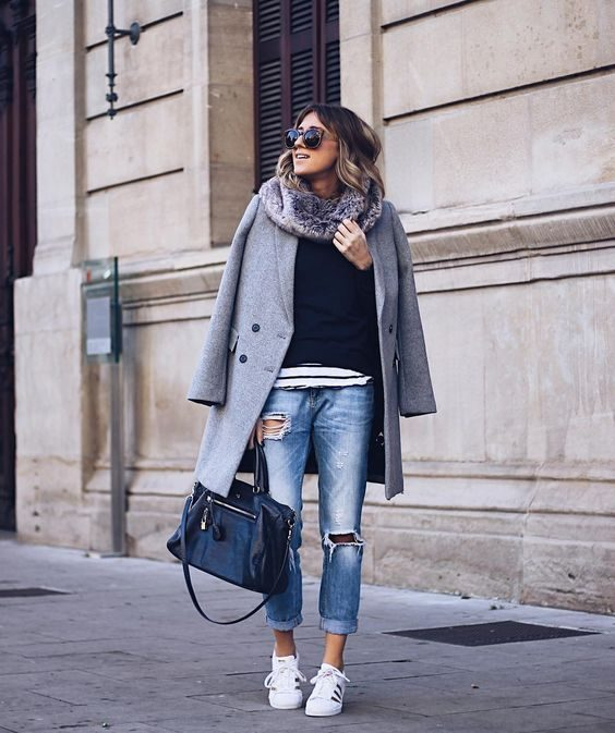 Ane Hernando is seen in a pair of faded denim jeans, with rip detailing, and rolled at the ankle. This she has then paired with gleaming Adidas sneakers, a navy blue top, and an oversized boyish grey coat. Shoes: Adidas.