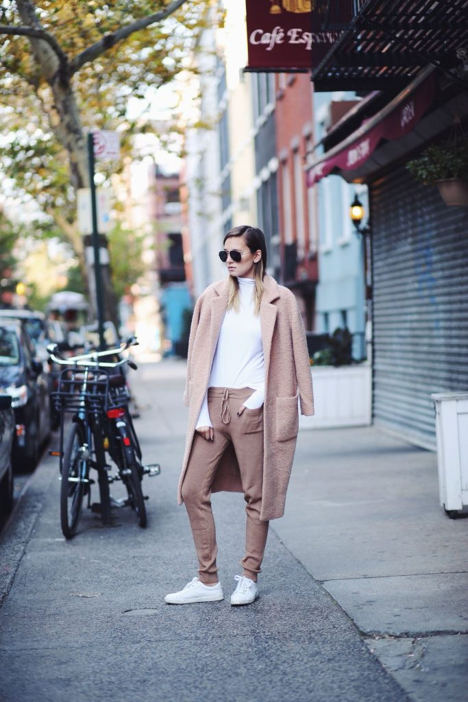 Danielle Bernstein is casual in a pair of nude joggers, worn with a matching overcoat, and plain white t-shirt with sneakers. Add shades to this look for a spring/summer must have. Coat: Ganni, Trousers: Zara, Top: Vince.