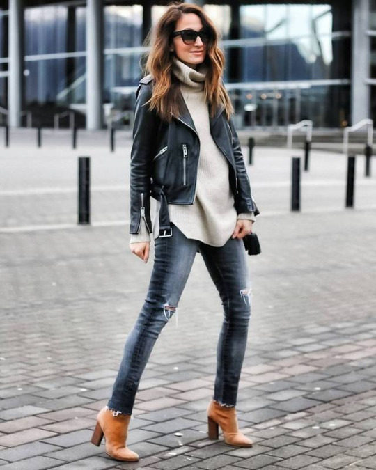 Cedar Atkins wears a belted leather jacket with a beige turtleneck sweater, skinny denim jeans, and a pair of suede heeled boots. This look is achievable, yet effortlessly chic. Jacket: All Saints, Jeans: Citizens of Humanity, Shoes: Alexander Wang.