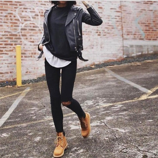 Petra wears a chunky black leather jacket over a black tee, layered over a white one for a striking contrast. She pairs this look with distressed black jeans and Timberland boots for a traditional biker chick style. Jacket: Acne Studios, Boots: Timberland.