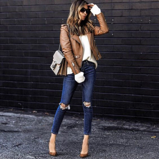 Sasha Simon wears a tan coloured leather jacket with a cream knit sweater and distressed denim jeans. Sasha matches the jacket with suede heels and chic shades. Brands not specified.