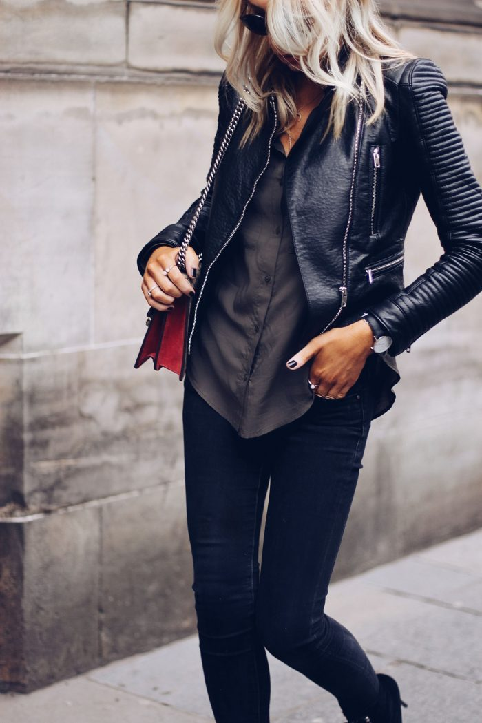 Lucy Connelly's leather jacket has been matched with a simple, silky button down shirt, black jeans, and minimal accessories. This stripped-back style is perfect for everyday wear. Brands not specified.