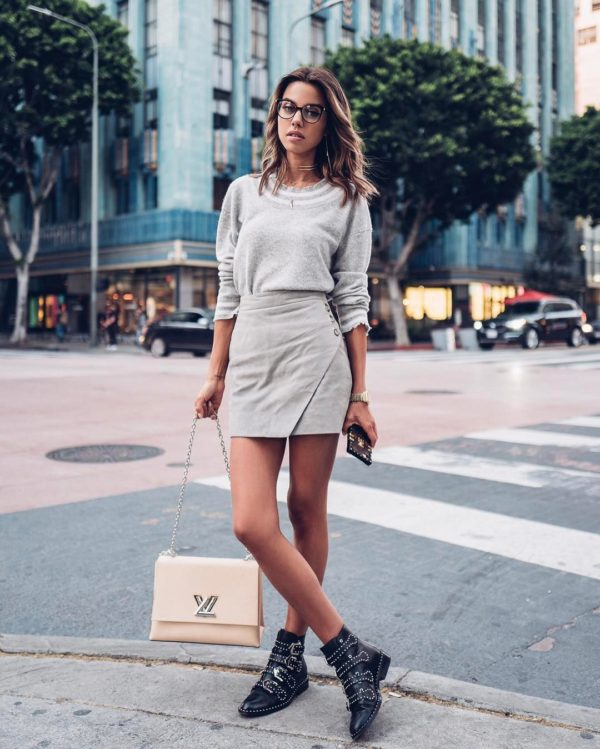Annabelle Fleur wears a pale grey wrapped mini skirt with a matching knit sweater of the same shade. Annabelle pairs this outfit with striking leather boots with stud detailing to giver her look a punk edge. Skirt: Givenchy.