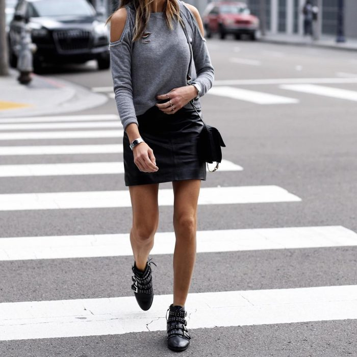 Stephanie Mooeny is wearing a cute leather min skirt, matched perfectly with buckled leather ankle boots with stud detailing. Stephanie wears this style with a shoulderless grey top and minimal jewellery. Skirt: Topshop.