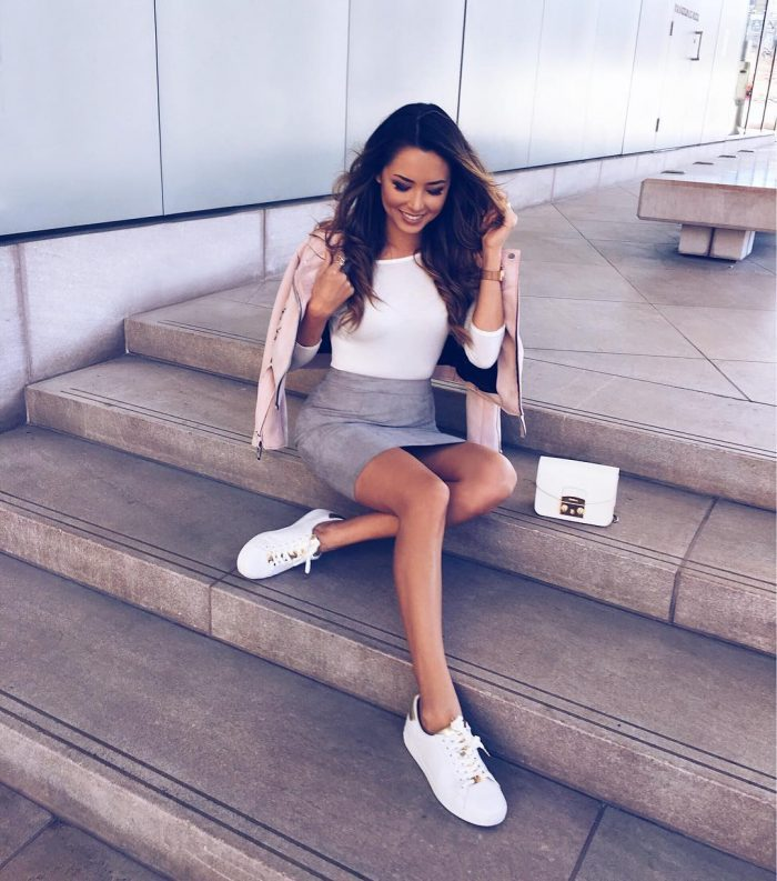 Jessica Ricks is wearing a suede mini skirt with a tight white tee and matching white sneakers, creating an urban street style which we love.. Jessica pairs this look with a blush pink biker style jacket. Coat: Zara, Skirt: Boohoo, Shoes: Michael Kors.