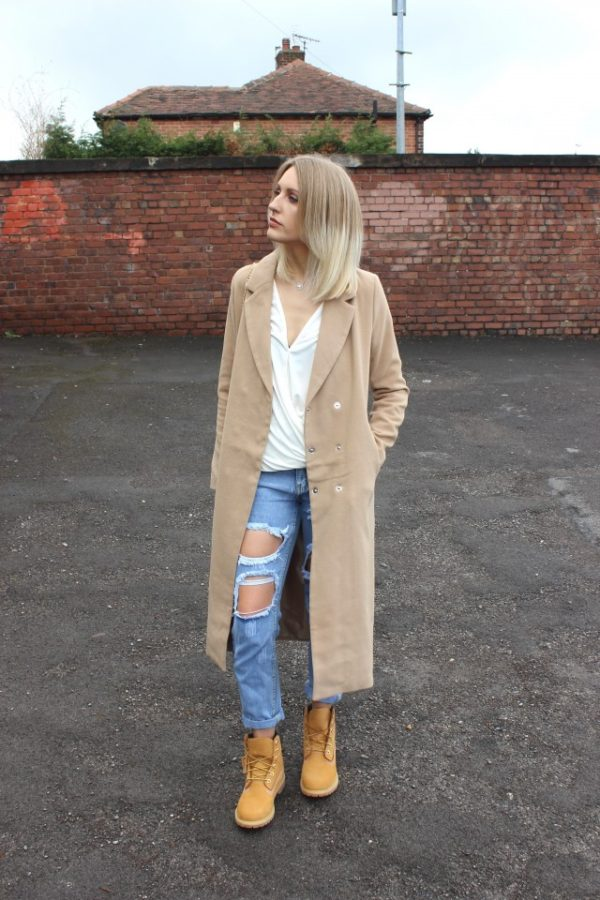 Destroyed jeans will look great worn with a pair of beige timberlands, as seen here worn by Charlotte Lewis. Wear this edgy look with a simple white V neck to accurately recreate this style. Jeans/Top/Coat/Bag: Pretty Little Thing, Boots: Timberland.