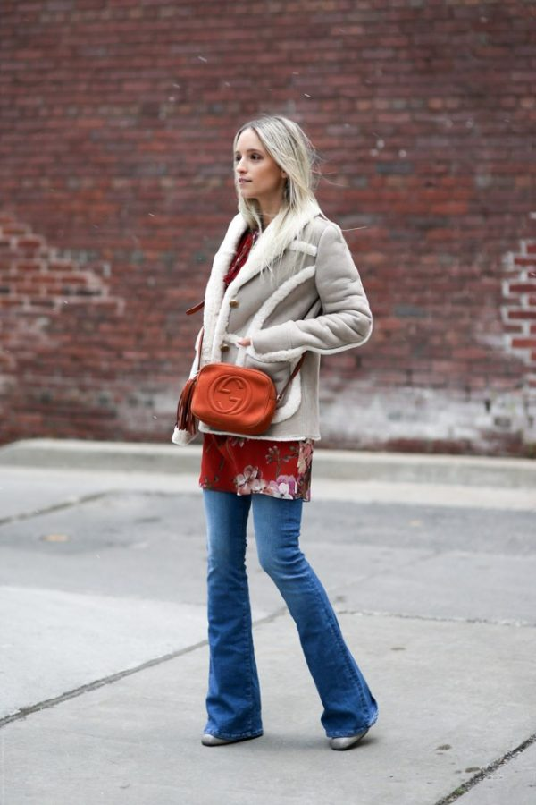 The shearling trend will look great worn with flared denim jeans and a floral top, as demonstrated here by Charlotte Groeneveld! Wear the look with pumps and a cross body bag to accurately recreate this cute winter look. Coat: Anothereight, Dress/Boots/Bag: Gucci, Jeans: MIH.