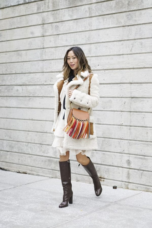 Chunky shearling coats are absolutely the ultimate winter item! Aimee Song presents a cosy and glamorous aesthetic here, pairing a statement coat with over the knee boots and a fringed leather bag. Coat/Dress: Chloe, Boots: Ralph Lauren.