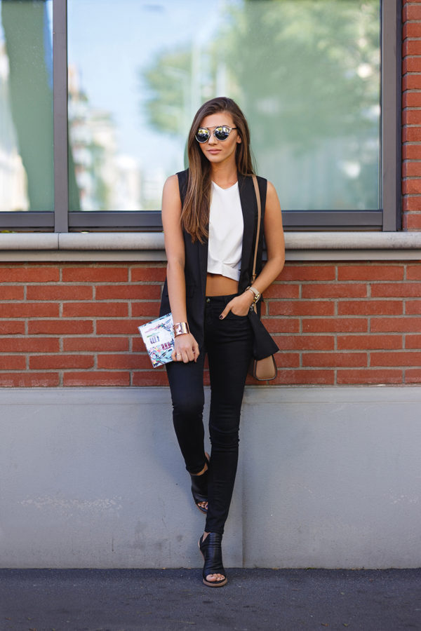 d4cc73fdb7df75 Larisa Costea pairs her black sleeveless jacket with a cute white crop top  and black denim jeans.