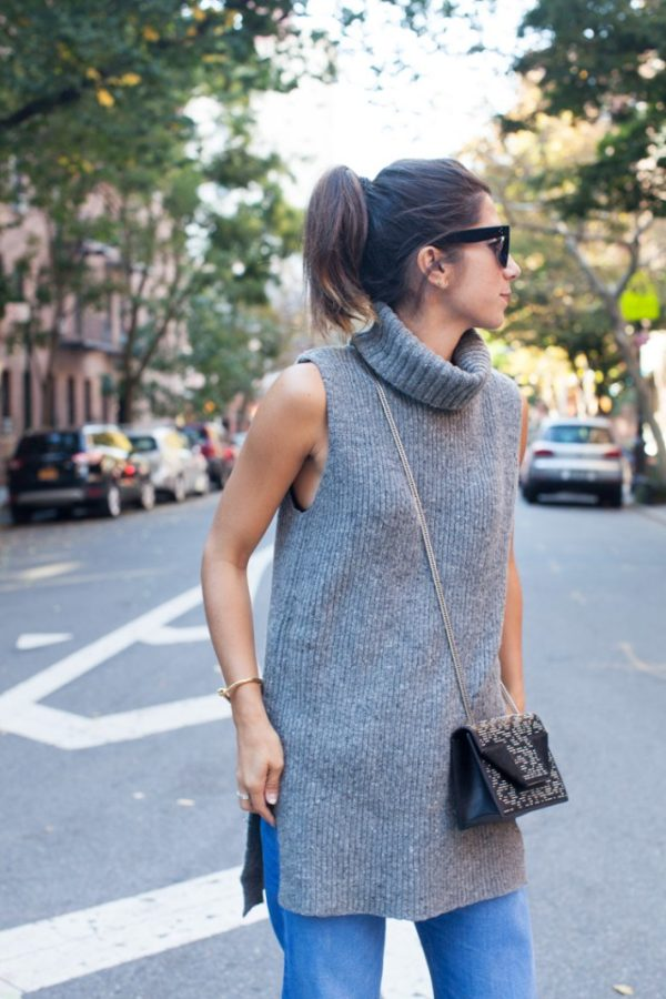 A thick knitted sleeveless turtleneck will look great worn with simple denim jeans and a cross body mini bag. Via Krystal Bick. Turtleneck: Macys; Jeans: MiH, Shoes: Saint Laurent.