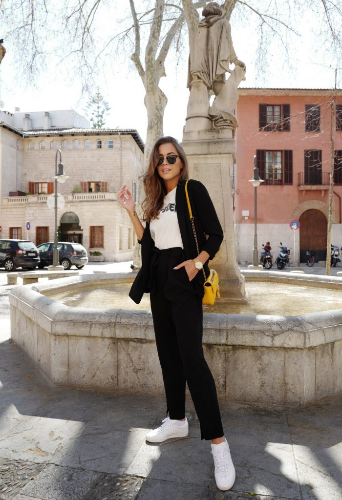 Kenza Zouiten is wearing slick black cigarette trouser tied at the waist, with a white graphic tee and a black cardi to create this spring look. She wears this outfit with bright white sneakers and a miniature yellow handbag. Blazer/Trousers/Tee: Gina Tricot.