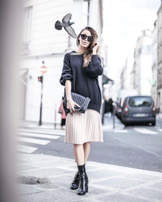 Pair a pleated midi skirt with an oversized sweater and patent leather boots to steal Julia Toivola's edgy spring style. She accessorises this look with a quilted leather handbag and shades. Brands not specified.