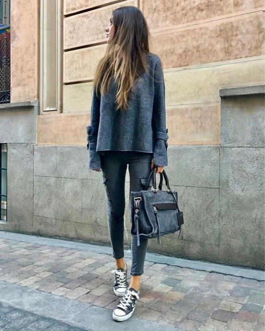 Maria Turiel Soler wears an all grey spring outfit, consisting of a long-sleeved top, denim jeans with oversized pocket detailing, and a pair of classic black converse. Jeans: Zara, Shoes: Converse.