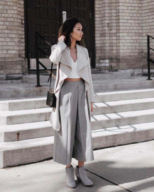 A gorgeously sophisticated spring look, Tina Hu wears flared grey culotte trousers with a cropped white top; all worn under a cream overcoat and paired with heeled suede boots. Top: Aritzia, Trousers: Zara, Bag: Celine, Shoes: Cole Haan.